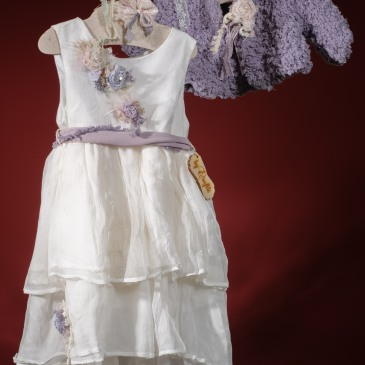 Ένα ονειρικό σύνολο για κορίτσι με βιολετί πινελιές που περιλαμβάνει: Φόρεμα (φόδρα από 100% βαμβάκι) λευκό πολυεπίπεδο με ζωνάκι και λεπτομέρρεια από χειροποίητα λουλούδια Στεφάνι με ασορτί λουλούδια Γιλέκο πλεγμένο στο χέρι με βελονάκι ή/και βιολετί μακρυμάνικο μπολερό