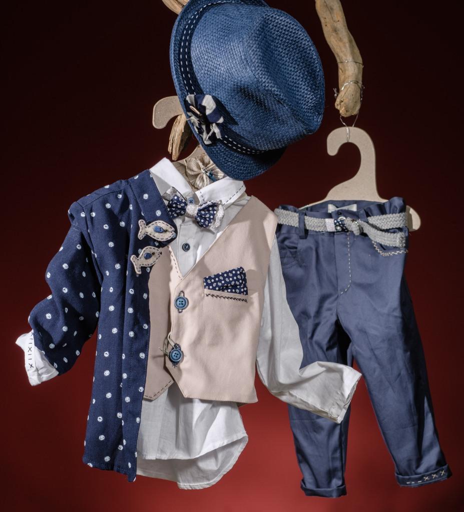 Ένα θεματικό βαφτιστικό σετ για αγόρι σε μπλε και εκρού που περιλαμβάνει Πουκάμισο λευκό με κέντημα Παντελόνι μπλε με πρωτότυπη ζώνη και κέντημα Γιλέκο εκρού με κεντημένες κουμπότρυπες και μαντήλι στο πέτο Καπέλο ψάθινο Σακάκι με βούλες και λεπτομέρειες από ψαράκια Παπιγιόν