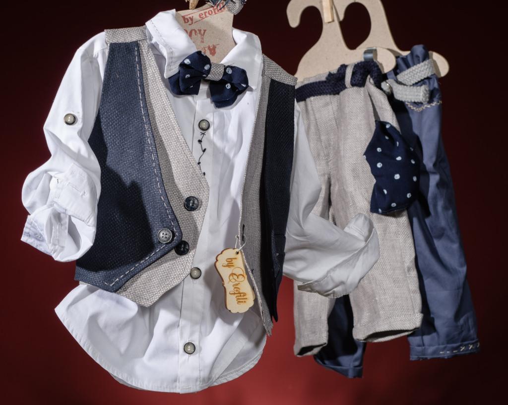 Ένα άνετο και διαχρονικό βαφτιστικό σετ για αγόρι σε απχρώσεις του μπλε που περιλαμβάνει:Πουκάμισο λευκό με κεντημένες κουμπότρυπες Παντελόνι γκρι ή μπλέ με κέντημα Γιλέκο διπλό μπλε-μπεζ Ζώνη Τζάκετ απο δερματίνη Παπιγιόν ή αντρικό φουλάρι