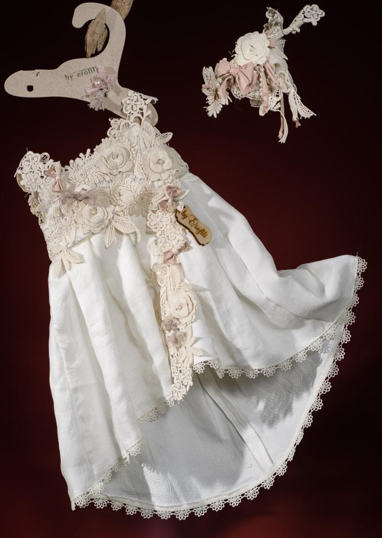 Ένα κρεμ βαφτιστικό σύνολο για κορίτσι με άφθονη δαντέλα που περιλαμβάνει:  Φόρεμα (φόδρα από 100% βαμβάκι) ασύμμετρο με δαντελένιο μπούστο, καταρράκτη δαντέλας στη φούστα και χειροποίητα υφασμάτινα λουλούδια  Στεφάνι με δαντέλα χειροποίητο  Για στιγμές γεμάτες γλύκα!