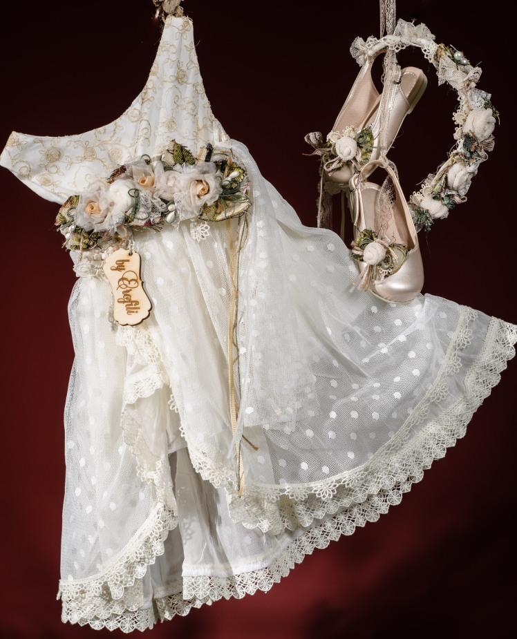 Ένα ντελικάτο βαφτιστικό σύνολο για κορίτσι με χρυσαφένιες λεπτομέρειες που περιλαμβάνει: Φόρεμα (φόδρα από 100% βαμβάκι) σε γραμμή Α με εμπριμέ χρυσό μπούστο, ζώνη από χειροποίητα υφασμάτινα λουλούδια και δαντελένιο τελείωμα Στεφανάκι ή καπελάκι με χειροποίητα λουλούδια Λουστρίνι παπουτσάκι ασορτί Για τις πιο λαμπερές στιγμές! Τιμή: 200 Ε + 60Ε παπουτσακια