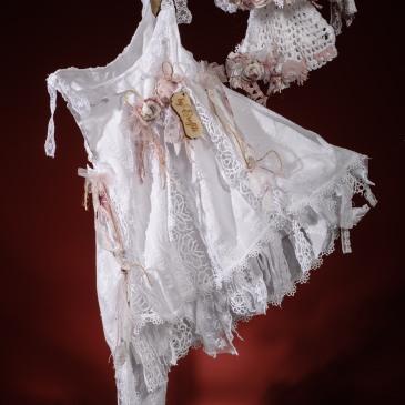 Ένα ελαφρύ βαφτιστικό σύνολο για κορίτσι με κομψή σιλουέτα που περιλαμβάνει: Φόρεμα (φόδρα από 100% βαμβάκι) με δαντελένιες λωρίδες που τονίζουν τη σιλουέτα Στεφανάκι ή καπελάκι με χειροποίητα λουλούδια Για στιγμές απόλυτης ξεγνοιασιάς!