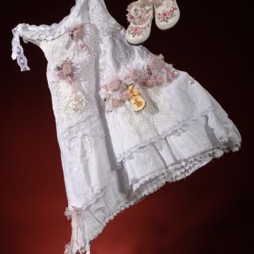 Ένα διασκεδαστικό βαφτιστικό σύνολο για κορίτσι με πολλά επίπεδα που περιλαμβάνει: Φόρεμα (φόδρα από 100% βαμβάκι) με ντεκολτέ χαμόγελο δετό στους ώμους με στρώσεις δαντέλας και σειρές από υφασμάτινα λουλούδια Στεφανάκι ή καπελάκι με χειροποίητα λουλούδια Παπουτσάκια μπαλαρίνες χειροποίητα και ζωγραφισμένα στο χέρι Για απόλυτη διάθεση παραμυθιού!