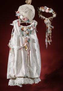 Ένα vintage βαφτιστικό σύνολο για κορίτσι με ζωηρές πινελιές χρωμάτων που περιλαμβάνει: Φόρεμα (φόδρα από 100% βαμβάκι) ντυμένο με δαντέλα με σούρα στο τελείωμα και χρωματιστά υφασμάτινα λουλούδια Στεφανάκι ή καπελάκι με χειροποίητα λουλούδια Για να πάρουν χρώμα οι μοναδικές στιγμές!