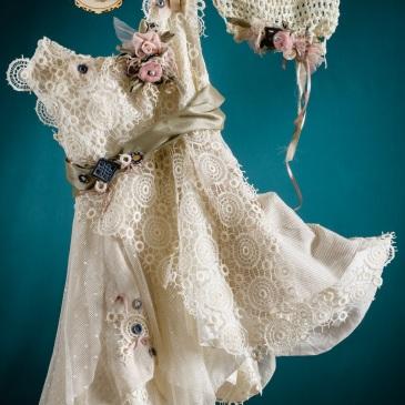 Ένα πρωτότυπο βαφτιστικό σύνολο για κορίτσι ιδιαίτερη σιλουέτα που περιλαμβάνει: Φόρεμα (φόδρα από 100% βαμβάκι) με δαντελένιο μπούστο, συνδυασμό υφασμάτων στη φούστα και ζώνη με υφασμάτινα λουλούδια και κεντημένες λεπτομέρειες Στεφανάκι με ασορτί χειροποίητα λουλούδια Για τις πιο περιπετειώδεις δεσποινίδες!