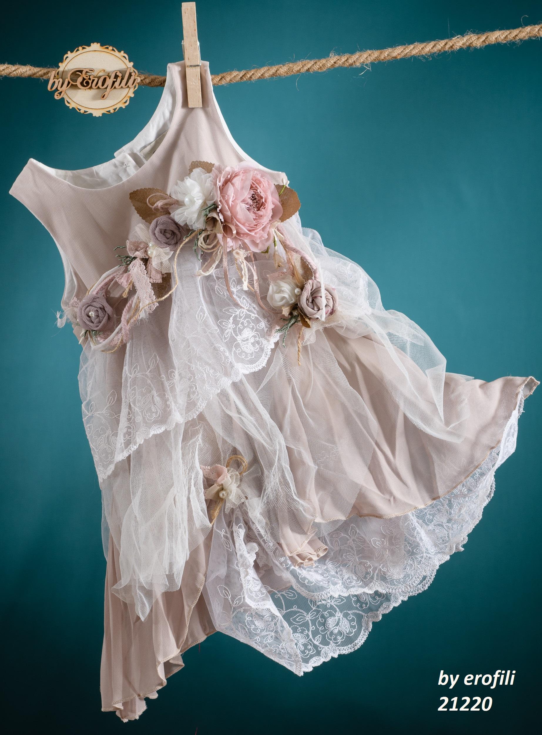 Ένα ρομαντικό ροζ βαφτιστικό σύνολο για κορίτσι με πολλές λεπτομέρειες που περιλαμβάνει:  Φόρεμα (φόδρα από 100% βαμβάκι) σε ροζ παστέλ, στολισμένο με χειροποίητα υφασμάτινα λουλούδια και έναν καταρράκτη από δαντέλες  Στεφανάκι ή καπελάκι με χειροποίητα λουλούδια