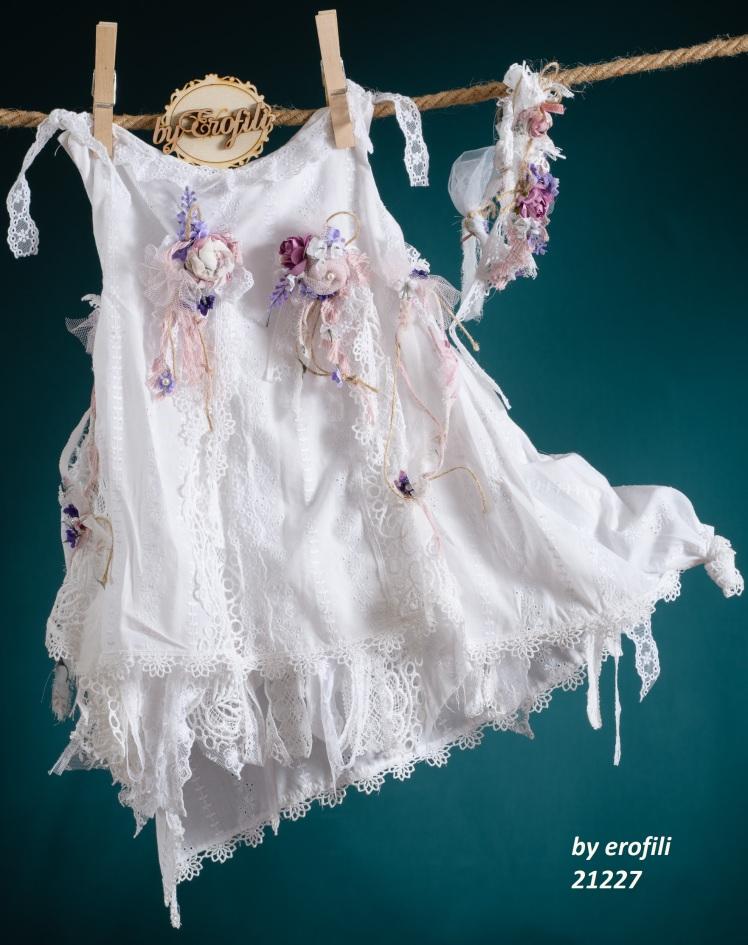 Ένα δροσερό βαφτιστικό σύνολο για σε άσπρες και μενεξεδί αποχρώσεις που περιλαμβάνει:  Φόρεμα (φόδρα από 100% βαμβάκι) λευκό από βαμβακερή δαντέλας με τούλινες λεπτομέρειες, στολισμένο με βιολετί και φούξια χειροποίητα υφασμάτινα λουλούδια Στεφανάκι ή καπελάκι με χειροποίητα λουλούδια