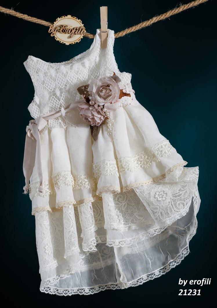 Ένα υπέρκομψο βαφτιστικό σύνολο για κορίτσια σε λευκό και χρυσό που περιλαμβάνει:  Φόρεμα (φόδρα από 100% βαμβάκι) λευκό από στρώσεις δαντέλας με τούλινες λεπτομέρειες, στολισμένο με ροζ χειροποίητα υφασμάτινα λουλούδια και πέρλες  Στεφανάκι ή καπελάκι με χειροποίητα λουλούδια